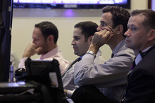 In this Tuesday, Oct. 23, 2012, photo, traders watch screens in a booth on the floor of the New York Stock Exchange. Stock futures are rising Tuesday, Oct. 24, 2012, ahead of the latest housing data and a report from China that could signal a recovery for the manufacturing sector of the world's second largest economy. (AP Photo/Richard Drew)