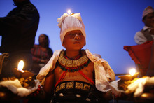 A young Nepalese Hindu devotee stands with burning oil lamps on his body as part of rituals to celebrate the tenth and final day of Dashain festival at Bhaktapur, also known as the city of devotees, on the outskirts of Katmandu, Nepal, Wednesday, Oct. 24, 2012. The festival commemorates the slaying of a demon king by Hindu goddess Durga, marking the victory of good over evil. (AP Photo/Niranjan Shrestha)