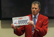 Francisco Kjolseth  |  The Salt Lake Tribune Paul Warner, executive director of America's Freedom Festival at Provo, shows off a representation of a new license plate they hope to get the state to produce with the words