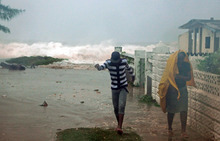 Residents evacuate their home as waves crash in the Caribbean Terrace neighborhood of eastern Kingston, Jamaica, Wednesday, Oct. 24, 2012. Hurricane Sandy pounded Jamaica with heavy rain as it headed for landfall near the country's most populous city on a track that would carry it across the Caribbean island to Cuba, and a possible threat to Florida. (AP Photo/Collin Reid)