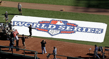 Workers paint a logo on the field at AT&T Park before workouts for baseball's World Series Tuesday, Oct. 23, 2012, in San Francisco. The Detroit Tigers play the San Francisco Giants in Game 1 on Wednesday, Oct. 24. (AP Photo/Eric Risberg)
