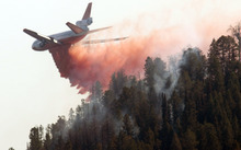 FILE - In this Sept. 12, 2012 file photo, a DC-10 air tanker drops its load of fire retardant as the the Horsethief Canyon Fire continues to burn near Jackson, Wyo. Wyoming saw one of its most destructive wildfire seasons  as wildfires across the state this year burned 75 homes, some 560,000 acres and cost about $100 million to fight. (AP Photo/ Jackson Hole News & Guide, Bradly J. Boner, File)  MANDATORY CREDIT; MAGS OUT; NO SALES