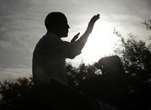 A silhouetted President Barack Obama gestures as he speaks during a morning campaign event at Ybor City Museum State Park, Thursday, Oct. 25, 2012, in Tampa, Fla. The president is on the second day of his 48 hour, 8 state campaign blitz. (AP Photo/Pablo Martinez Monsivais)