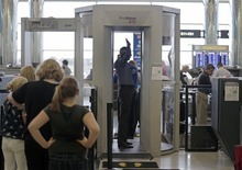 In this Wednesday, Oct. 24, 2012 photo, passengers are scanned at a Terminal C security checkpoint at Logan Airport in Boston using a millimeter wave body scanner, which produces a cartoon-like outline rather than naked images of passengers produced by a similar machine using X-rays. The Transportation Security Administration is deploying more of the millimeter wave machines at seven major U.S. airports where the agency is removing all of the full-body X-ray scanners that have been criticized by privacy advocates. (AP Photo/Charles Krupa)