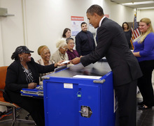 President Barack Obama, right, turns in his ballot receipt to election official Marie Holmes, left, as he prepares to cast his vote, during early voting, in the 2012 election at the Martin Luther King Community Center, Thursday, Oct. 25, 2012, in Chicago. (AP Photo/Pablo Martinez Monsivais)
