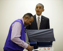 President Barack Obama, right, reacts to election official Eli Selph's cell ringing as he casts his vote, during early voting, in the 2012 election at the Martin Luther King Community Center, Thursday, Oct. 25, 2012, in Chicago. (AP Photo/Pablo Martinez Monsivais)