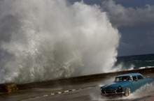 Ramon Espinosa  |  The Associated Press A driver maneuvers his classic American car along a wet road as a wave crashes against the Malecon in Havana, Cuba, Thursday, Oct. 25, 2012.  Hurricane Sandy blasted across eastern Cuba on Thursday as a potent Category 2 storm and headed for the Bahamas after causing at least four deaths in the Caribbean.