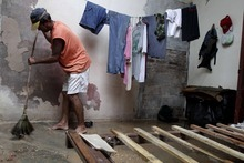 Jose Aguilera seeps his home's floor by his empty bed frame after the passing hurricane Sandy damaged his roof, causing rain to soak his mattress, in Gibara, Cuba, Thursday, Oct. 25, 2012. Hurricane Sandy blasted across eastern Cuba on Thursday as a potent Category 2 storm and headed for the Bahamas after causing at least two deaths in the Caribbean. (AP Photo/Franklin Reyes)