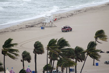A Fort Lauderdale Ocean Rescue truck drives past a lifeguard stand on an empty beach, Thursday, Oct. 25, 2012 in Fort Lauderdale, Fla. Hurricane Sandy was expected to churn through the central and northwest Bahamas late Thursday and early Friday. It also might bring tropical storm conditions along the southeastern Florida coast, the Upper Keys and Florida Bay by Friday morning. (AP Photo/Wilfredo Lee)