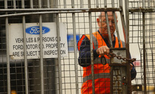 A security guard locks a gate after workers left the Ford Transit Assembly Plant in Southampton, England  after being told that the site will close with the loss of up to 1,500 jobs Thursday Oct. 25, 2012. Ford, which expects to lose more than $1 billion a year in Europe, has been pursuing plant closures and layoffs. Fears were mounting that the axe may also soon fall in Britain as trade unions at Ford's Southampton plant have been called in for a meeting with management on Thursday. (AP Photo/Chris Ison/PA) UNITED KINGDOM OUT NO SALES NO ARCHIVE