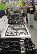 In this Monday, Sept. 10, 2012 photo Brian Gibson, center, and his wife Elizabeth Gibson, right, both of Framingham, Mass., examine stoves at a Lowe's store location in Framingham. U.S. companies remained cautious in September and held back on orders for long-lasting manufactured goods that signal investment plans.  (AP Photo/Steven Senne)