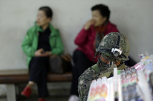 A South Korean soldier takes a position as women sit on the bench during an anti-terror drill at a subway station in Seoul, South Korea, Thursday, Oct. 25, 2012. (AP Photo/Lee Jin-man)