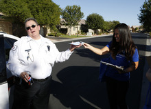 Utah republican Linda Patiño, right, offers early voting information to security guard Lee Rose after Rose cited her for canvasing homes in Las Vegas on Saturday, Oct. 20, 2012. (Isaac Brekken for the Salt Lake Tribune)