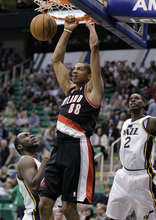Portland Trail Blazers forward Nicolas Batum (88) dunks as Utah Jazz's Al Jefferson, left, and Marvin Williams (2) watch during the first quarter of a preseason NBA basketball game Thursday, Oct. 25, 2012, in Salt Lake City. (AP Photo/Rick Bowmer)