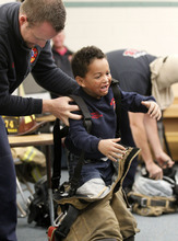 Al Hartmann  |  The Salt Lake Tribune West Valley City firefighter Mike Reardon, left,  helps Whittier Elementary School student Mason Fackrell put on a firefighting suit. Mason was severly burned on his face and hands when he was a toddler. Firefighters aimed to help classmates of the now 6-year-old understand what happened to him.