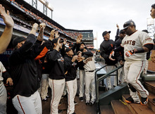 San Francisco Giants' Pablo Sandoval is congratulated by teammates after hitting a home run during the first inning of Game 1 of baseball's World Series against the Detroit Tigers Wednesday, Oct. 24, 2012, in San Francisco. (AP Photo/David J. Phillip)