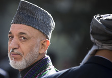 Afghan President Hamid Karzai turns around after reviewing the guard of honor during the first day of Eid Al Adha celebrations at the palace in Kabul, Afghanistan, Friday, Oct 26, 2012. Karzai called on Taliban to embrace peace and to join the government and lay down their arms. (AP Photo/Anja Niedringhaus)