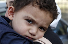 Bushr Al Tawashi looks at the photographer as he is carried by his mother Arin Al Dakkar, outside of a private Sigma TV station, in Nicosia, Cyprus, Friday, Oct. 26, 2012. A 2-year-old Syrian boy who was believed dead after his family inadvertently left him behind as they fled shelling in Damascus last summer has been reunited with his parents in Cyprus, a lawyer said.