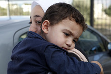 Bushr Al Tawashi, as he is carried by his mother Arin Al Dakkar, outside of a private Sigma TV station, in Nicosia, Cyprus, Friday, Oct. 26, 2012. A 2-year-old Syrian boy who was believed dead after his family inadvertently left him behind as they fled shelling in Damascus last summer has been reunited with his parents in Cyprus, a lawyer said.