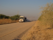A truck travels along the stretch of gravel road in southern Texas, Friday Oct. 26, 2012, where a Texas Department of Public Safety helicopter and sharpshooter assisted the previous day in the chase of a suspected illegal immigrant smuggler. Two people in the fleeing vehicle were killed and a third was wounded. (AP Photo/Chris Sherman)