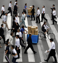 FILE - In this Sept. 28, 2012 file photo, people cross a street in Tokyo.  Japan's Cabinet approved a 423 billion yen ($5.3 billion) economic stimulus package on Friday, Oct. 26, 2012,  moving to fend off recession amid signs the recovery in the world's third biggest economy is faltering.  (AP Photo/Koji Sasahara, File)