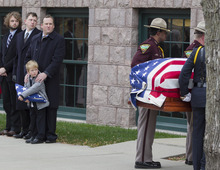 Will Mead holds a tri-folded flag as he watches with family members the casket of his great grandfather, former Democratic U.S. Senator and three-time presidential candidate George McGovern, being carried into the Washington Pavilion of Arts and Science in Sioux Falls, S.D., for the funeral service, Friday, Oct. 26, 2012. McGovern died Sunday in his native South Dakota at age 90. (AP Photo/Nati Harnik)