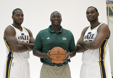 In this Oct. 1, 2012, photo, Utah Jazz coach Tyrone Corbin, center, and Jazz's Paul Milsap, left, and Al Jefferson pose for a photograph during the NBA basketball team's media day in Salt Lake City. Utah has perhaps the best set of