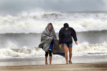 McKayla Walker and her mother, Holly, fight the wind and enjoy their first time to see hurricane waves on the Atlantic Ocean, Saturday, Oct. 27, 2012 in Atlantic Beach, N.C.  (AP Photo/The Jacksonville Daily News, Chuck Beckley)