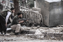 In this Friday, Oct. 26, 2012 photo, Syrian rebel fighters take cover as a Syrian army sniper aims over a destroyed mosque in Tarik Al-Bab, southeast of Aleppo, Syria. Activists say Syrian troops have shelled rebel-held areas and clashed with anti-government gunmen in several parts of the country despite an internationally mediated cease-fire. The Britain-based Syrian Observatory for Human Rights and the Local Coordination Committees report shelling and shooting mostly in the northern province of Aleppo, the eastern region of Deir el-Zour, Daraa to the south and suburbs of the capital Damascus. (AP Photo/Narciso Contreras)