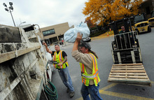 Baltimore Gas & Electric (BGE) workers Jordan Sauer, left, and William MacAleese, load plastic bags to be filled with sand at a BGE storage yard in Baltimore Friday, Oct. 26, 2012. Utilities and governments on the East Coast are preparing for Hurricane Sandy, which is expected to bring extreme weather to the region beginning Sunday. (AP Photo/Steve Ruark)