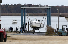 As another boat waits its turn, a 50-ton lift raises Fancy Nancy, a 40-foot commercial fishing boat, out of the Maurice River at Yank Marine Services marina Saturday, Oct. 27, 2012, in Dorchester, N.J., in preparation for Hurricane Sandy. From the lowest lying areas of the Jersey Shore, where residents were already being encouraged to leave, to the state's northern highlands, where sandbags were being filled and cars moved into parking lots on high ground, New Jersey began preparing in earnest for Sandy. (AP Photo/Mel Evans)