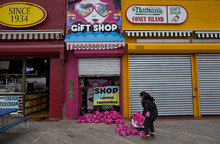 Jessie Rivera, 10, of New York, a young customer of the Lola Star Gift Shop on the Coney Island boardwalk, brings pink sandbags to the door of the shop Sunday, Oct. 28, 2012, in New York. Tens of thousands of people were ordered to evacuate coastal areas Sunday as big cities and small towns across the U.S. Northeast braced for the onslaught of a superstorm threatening some 60 million people along the most heavily populated corridor in the nation.. (AP Photo/Craig Ruttle)