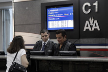 The flight standby list is displayed as a couple of gate agents assist a passenger at LaGuardia airport, Sunday, Oct. 28, 2012 in New York. Tens of thousands of residents were ordered to evacuate coastal areas Sunday as big cities and small towns across the Northeast buttoned up against the onslaught of a superstorm. (AP Photo/Mary Altaffer)