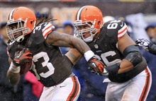 Cleveland Browns running back Trent Richardson (33) gets a shove from guard Shawn Lauvao on his way to a 26-yard touchdown against the San Diego Chargers in the first quarter of an NFL football game in the rain on Sunday, Oct. 28, 2012, in Cleveland. (AP Photo/Tony Dejak)