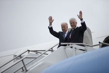 Vice President Joe Biden and former President Bill Clinton wave as they walk out of Air Force Two during a rainstorm,  Monday, Oct. 29, 2012, in Youngstown, Ohio. (AP Photo/Matt Rourke),