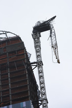 A construction crane atop a luxury high-rise dangles precariously over the streets after collapsing in high winds from Hurricane Sandy, Monday, Oct. 29, 2012, in New York. Hurricane Sandy continued on its path Monday, as the storm forced the shutdown of mass transit, schools and financial markets, sending coastal residents fleeing, and threatening a dangerous mix of high winds and soaking rain. (AP Photo/ John Minchillo)