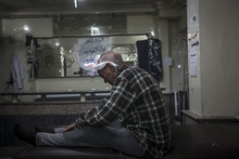In this Saturday, Oct. 27, 2012 photo, a Syrian elder sits on a hospital trolley suffering partial loss of memory after was shot in the head by a sniper while walking on a street in Bustan Al-Pasha, Aleppo, Syria. (AP Photo/Narciso Contreras).