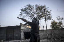 In this Saturday, Oct. 27, 2012 photo, a rebel fighter looks over the street as he prepares himself to run through a sniper line-of -fire in the southeast area of Aleppo, Syria. (AP Photo/Narciso Contreras).