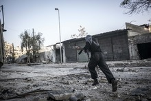 In this Saturday, Oct. 27, 2012 photo, a rebel fighter runs for cover through a sniper line-of-fire, in the southeast area of Aleppo, Syria. (AP Photo/Narciso Contreras).