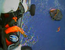 In this image made from video and released by the U.S. Coast Guard, a USCG rescue swimmer, in water at right, and a crew member use a hoist to bring up a survivors into a helicopter. A replica tall ship caught in Hurricane Sandy's wrath began taking on water, forcing the crew to abandon the boat Monday in rough seas off the North Carolina coast. The Coast Guard rescued 14 crew members by helicopter, but two people were still missing. (AP Photo/U.S. Coast Guard)