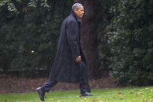 After canceling his appearance at a morning campaign rally in Orlando, Fla., President Barack Obama walks toward the White House in a driving rain after returning to Washington to monitor preparations for early response to Hurricane Sandy, Monday, Oct. 29, 2012. (AP Photo/Jacquelyn Martin)