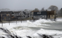 Ocean waves kick up near homes along Peggoty Beach in Scituate, Mass. Monday, Oct. 29, 2012. Hurricane Sandy continued on its path Monday, as the storm forced the shutdown of mass transit, schools and financial markets, sending coastal residents fleeing, and threatening a dangerous mix of high winds and soaking rain. (AP Photo/Elise Amendola)