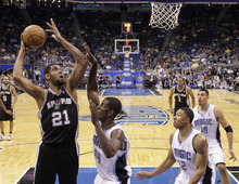 San Antonio Spurs' Tim Duncan (21) takes a shot over Orlando Magic's Andrew Nicholson (44) as Justin Harper (32) and Gustavo Ayon (19), of Mexico, look on, during the first half of an NBA preseason basketball game, Sunday,Oct. 21, 2012, in Orlando, Fla. Orlando won 104-100.(AP Photo/John Raoux)