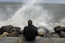 Lamar Chambers watches waves as winds from hurricane Sandy reach Seaside Park in Bridgeport, Conn., Monday, Oct. 29, 2012. Hurricane Sandy continued on its path Monday, forcing the shutdown of mass transit, schools and financial markets, sending coastal residents fleeing, and threatening a dangerous mix of high winds and soaking rain.  (AP Photo/Jessica Hill)