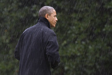 After canceling his appearance at a morning campaign rally in Orlando, Fla., President Barack Obama walks into the White House in a driving rain after returning to Washington to monitor preparations for early response to Hurricane Sandy, Monday, Oct. 29, 2012. (AP Photo/Jacquelyn Martin)