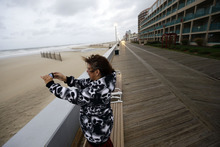 Mary Corrus, from Ocean City, Md., takes a picture of the rough surf as Hurricane Sandy bears down on the East Coast, Sunday, Oct. 28, 2012, in Ocean City, Md.  Governors from North Carolina, where steady rains were whipped by gusting winds Saturday night, to Connecticut declared states of emergency. Delaware ordered mandatory evacuations for coastal communities by 8 p.m. Sunday. (AP Photo/Alex Brandon)
