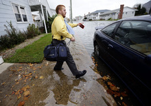 Cody Billotte walks through the high water as he gets in his car to go to work as Hurricane Sandy bears down on the East Coast, Sunday, Oct. 28, 2012, in Ocean City, Md. Governors from North Carolina, where steady rains were whipped by gusting winds Saturday night, to Connecticut declared states of emergency. Delaware ordered mandatory evacuations for coastal communities by 8 p.m. Sunday. (AP Photo/Alex Brandon)