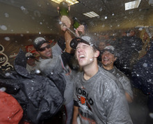 Buster Posey is sprayed with champagne in the locker room as San Francisco Giants celebrate after the Giants defeated the Detroit Tigers, 4-3, in Game 4 of baseball's World Series  Sunday, Oct. 28, 2012, in Detroit. The Giants won the World  Series 4-0. (AP Photo/David J. Phillip)